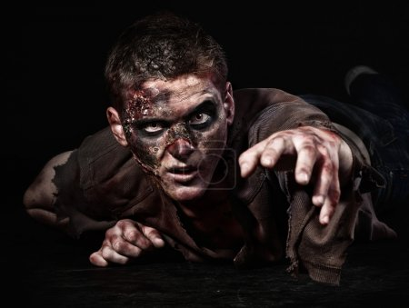 Photo for The scary zombie is lying in the studio and stretching - Royalty Free Image