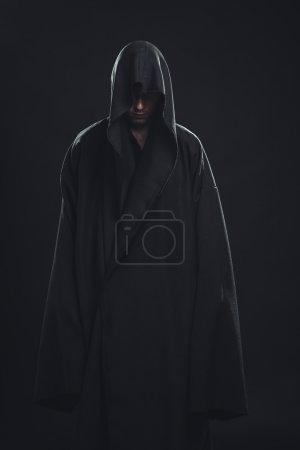 Photo pour Portrait d'un homme en robe noire sur fond sombre - image libre de droit