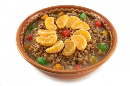 Traditional Christmas dish.Sweet wheat porridge with dried fruit, lobules tangerine and honey in a clay bowl