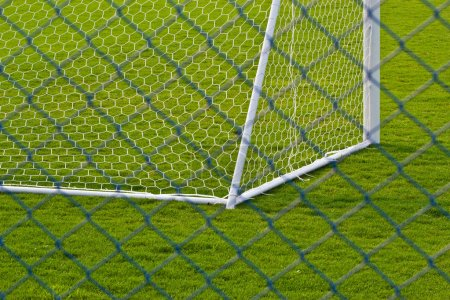 Goalpost net detail with green grass blur in background sports c