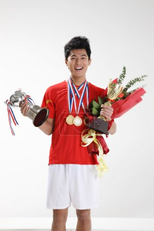Smiling asian sportsman with trophies and medals