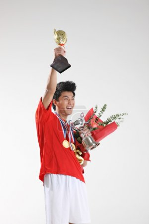Handsome asian sportsman with trophies and medals