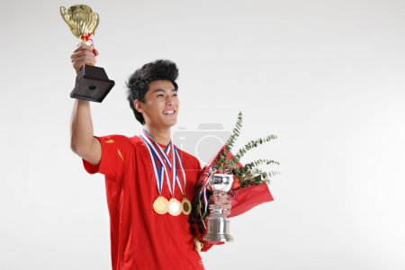 Asian sportsman with trophies and medals