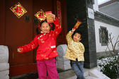 Two children(5-18 years) standing in front of chinese traditiona