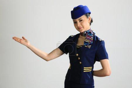 Chinese flight attendant gesturing