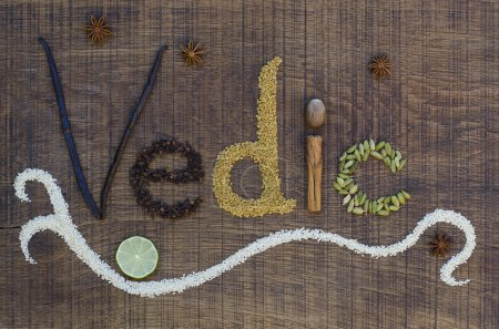 The word Vedic spelled out in ayurveda spices and seeds on a wooden board