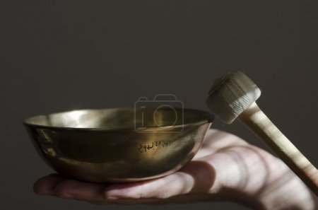 Photo for A Tibetan singing bowl sitting in a hand being played with a baton. - Royalty Free Image