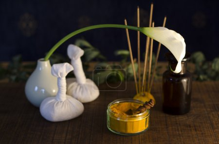 Photo for A table top arrangement of spice, oil and massaging tools, used in Ayurveda massage. - Royalty Free Image