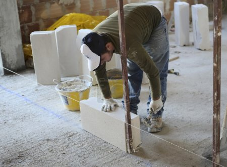 Ricklayer sets the construction of a partition wall with aerated concrete blocks
