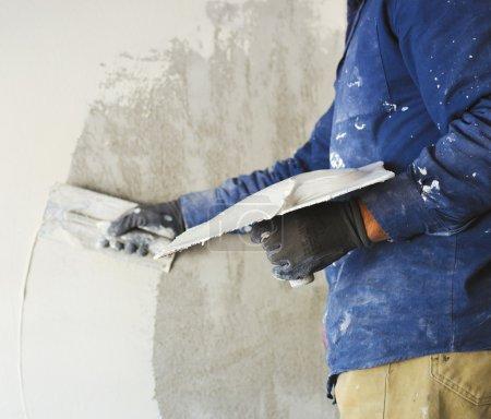 travailleur plâtrage marbre plâtre outil sur plâtre intérieur brut