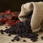 Black raisins in burlap bag over wooden table...