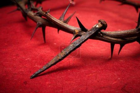 Foto de Semana de pasión. corona de Jesús christ de espinas y un clavo sobre fondo rojo - Imagen libre de derechos