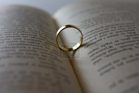 Close up of wedding ring lying on an open book
