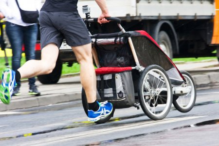 Photo for Father run with baby stroller in marathon - Royalty Free Image