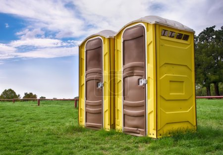 Photo for Two yellow portable toilets at a park - Royalty Free Image