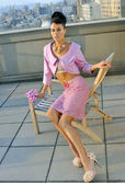 Model wearing pink couture designer clothes on rooftop
