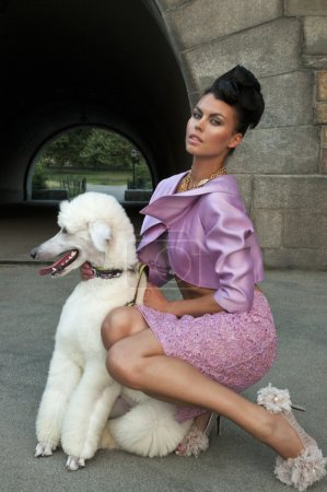 Model holding a white dog wearing pink couture designer clothes