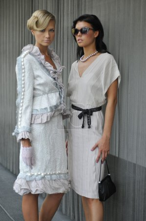 Portrait of two models wearing couture designer gowns