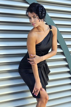 Model wearing small black couture designer dress