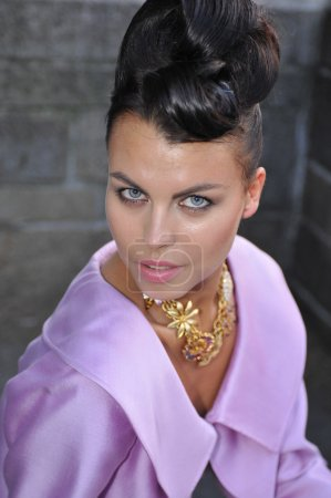 Portrait of fashion model wearing pink dress and gold jewelry