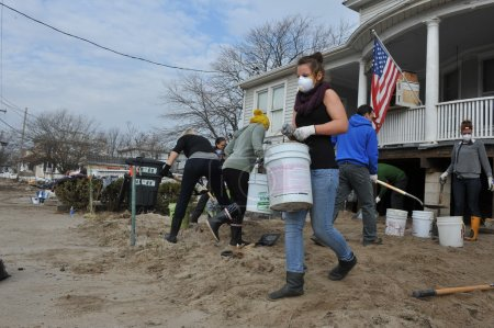 QUEENS, NY - NOVEMBER 11: Volunteers cleaning sand in the Rockaway Beach residential area after Hurricane Sandy in Queens, New York, U.S., on November 11, 2012.