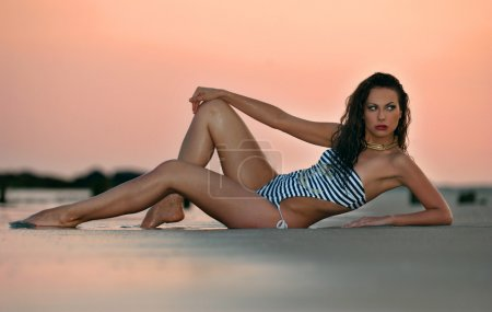 Beautiful brunette posing sexy at the beach during golden sunset time