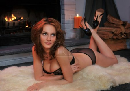Beautiful tall redhead dressed in elegant lingerie laying in the rug at front of working fireplace