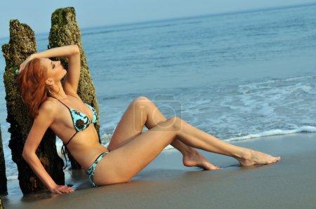 Pretty woman in blue bikini arching her back on a beach