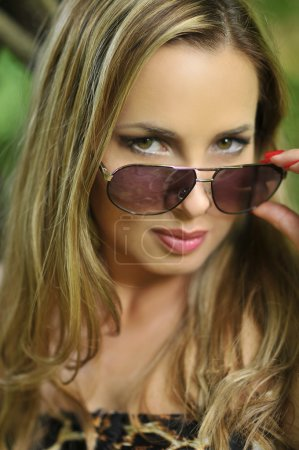 Portrait of beautiful fashion model with glamor make-up and sunglasses posing on exotic location