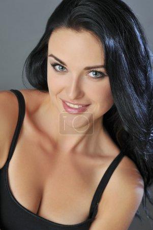 Photo pour Souriante séduisante jeune femme brune aux yeux bleus - image libre de droit