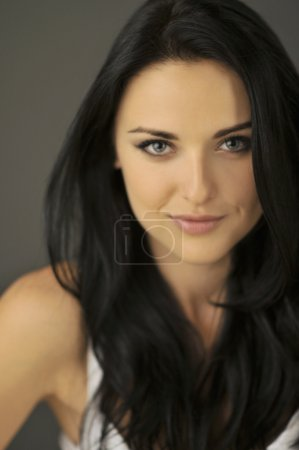 Photo for Attractive smiling young brunette woman with blue eyes. Shallow depth of field, focus on eyes. - Royalty Free Image