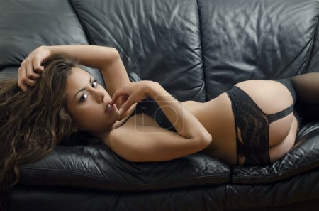 Photo for Portrait of young brunette woman posing sexy in lingerie at black leather sofa love seat - Royalty Free Image