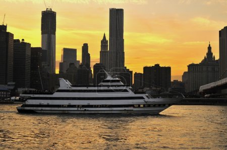 A river cruise boat on the East River heading under the Brooklyn Bridge in New York City at sunset time.