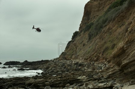 Helicopter flying over rocky beach in Palos Verdes, CA