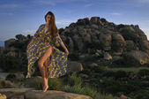 An attractive young woman wearing a designe's bikini and beach dress stands in front of a rock. Stony Point park, Topanga Canyon Blvd, Chatsworth, CA