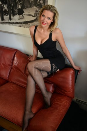 Sexy girl wearing black lingerie posing on the sofa