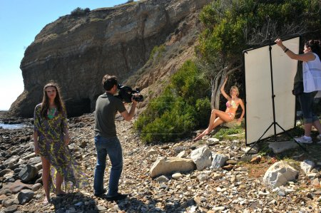 Photo video crew on location set with bikini models