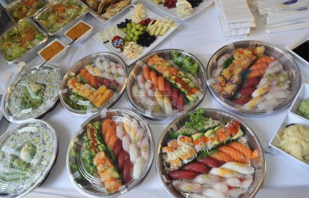 Sushi, sashimi, rolls on trays and cold snacks