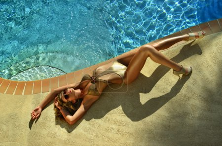 Fashion model posing pretty by swimming pool wearing designers one piece swimsuit and sunglasses