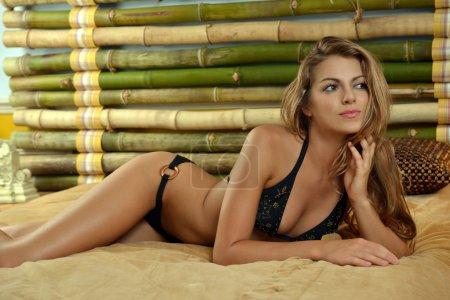 Fashion model posing pretty at bamboo bedroom interior wearing designers bikini and custom jewelery