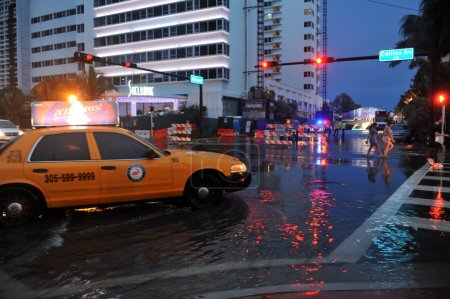 Cars moving on flooded streets and roads of Miami South Beach