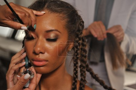 Model getting ready for the show at the Agua Di Lara 2014 Collection backstage during Mercedes-Benz Swim Fashion Week