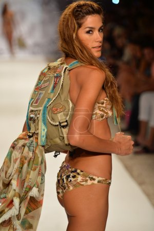 Model walks runway with backpack at the Agua Bendita Collection for Spring - Summer 2014