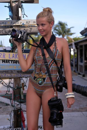 Photo pour Modèle tenant trois appareils photo professionnels à l'emplacement tropical de Key West, FL avec un vieux panneau indicateur à l'arrière-plan - image libre de droit