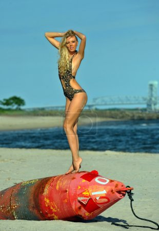 Blonde woman posing on a beach