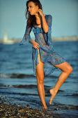 Žena, která pózuje na pláži v šatech
