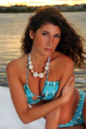 Brunette wearing pearl necklace and blue bikini
