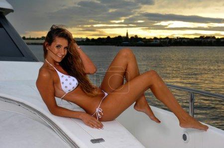 Seductive model posing on sailboat in sunset