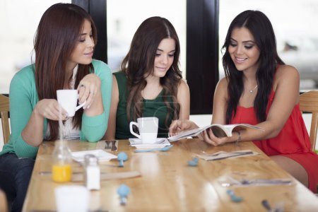Photo for Three young women looking magazine - Royalty Free Image