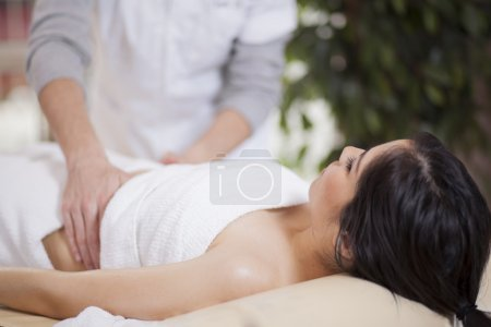 Closeup of a natural mature woman having a massage of her abdomen